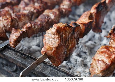 Grilled kebab on metal skewer, closeup. Roasted meat cooked at barbecue. BBQ fresh beef meat chop slices. Traditional eastern dish, shish kebab. Grill on charcoal and flame, picnic, street food