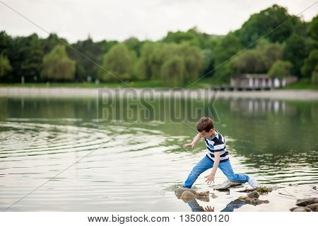 little boy lost his balance and went into the lake
