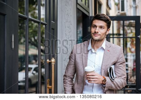 Handsome young man with coffee and newsaper walking along the street in the city