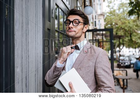Funny nerd man wearing eyeglasses and bow at the cafe outdoors