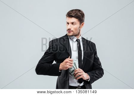 Serious young businessman in suit and tie hiding money in pocket over white background