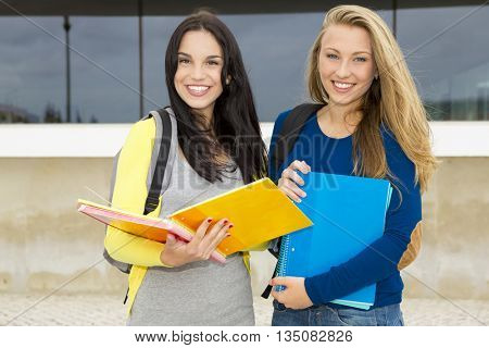 Two happy and beautiful teenage students in the school