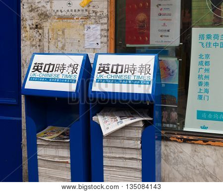 LONDON ENGLAND - OCTOBER 19 2015: Stand with free UK china times news papers in chinatown London situated in the Soho district