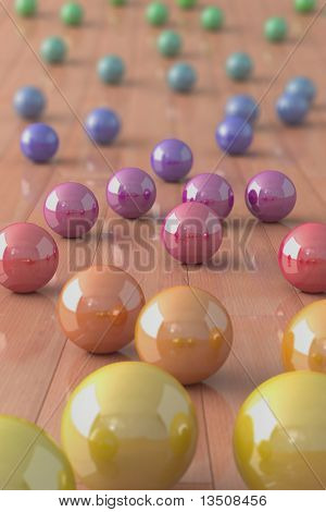 Colorful marble balls on a parquet floor