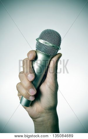closeup of a young caucasian man with a microphone in his hand, with a vignette added