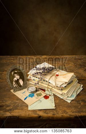 Antique portrait of a woman and a bundle of old letters on a wooden table