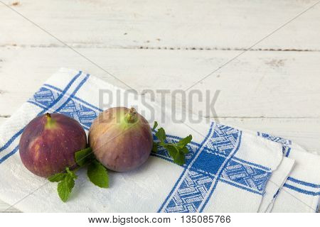 Two fresh figs on a textured vintage wooden table