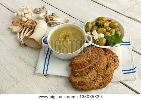 Grunge table board with soup and edible mushrooms