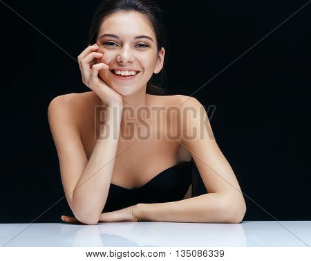 Smiling brunette girl on dark background. Youth and skin care concept