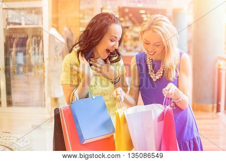 Woman showing her purchase to her best friend
