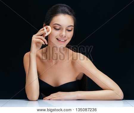 Woman applying cushion for powder. Photo young woman of european appearance on black background. Youth and skin care concept
