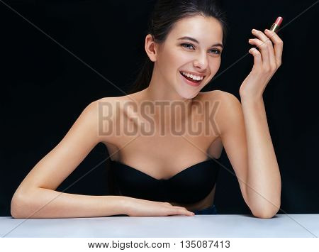 Happy brunette girl with lipstick on black background. Youth and skin care concept