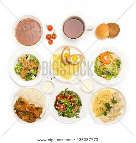 Top view of many plates with food over white background