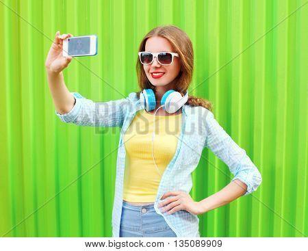Pretty Cool Girl Makes Self Portrait On Smartphone Over Green Ba