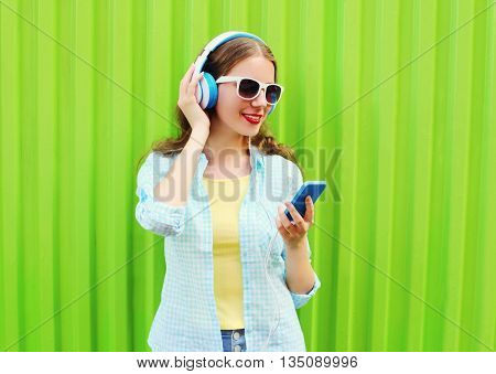 Pretty Cool Woman Listens To Music In Headphones Using Smartphon