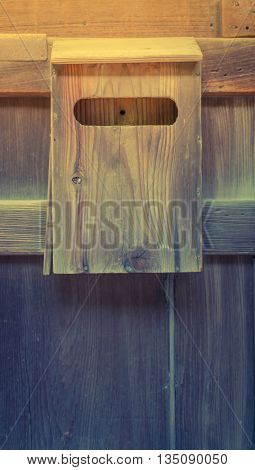 Old wooden mailbox on wood background  ( Filtered image processed vintage effect. )
