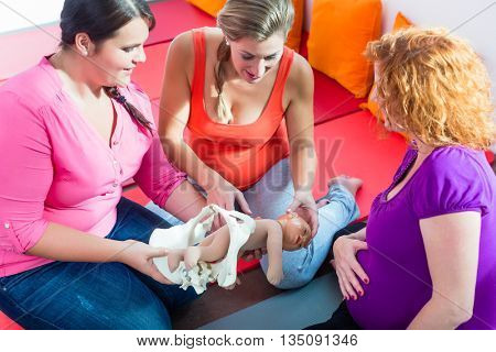 Midwife explaining birth process to pregnant women during antenatal class with anatomic model of pelvic bone