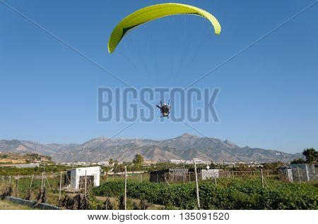 A yellow motor- driven paraglider flying a few meters above the ground on a beautiful sunny day with blue sky and no clouds and some mountains in the background.