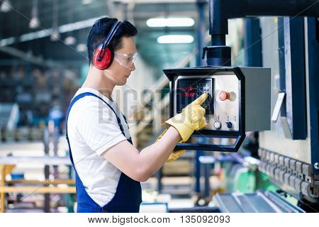Asian worker operating CNC metal skip in factory on the machine floor