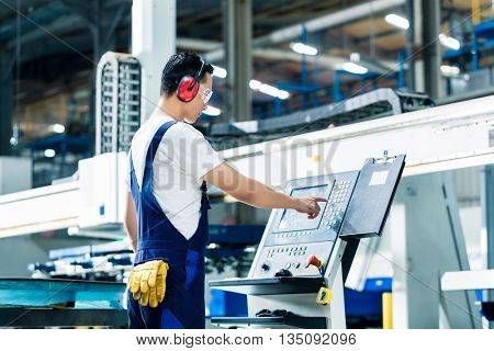 Worker entering data in CNC machine at factory floor to get the production going
