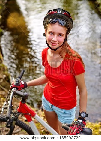 Bicycle girl. Girl wearing bicycle helmet rides bicycle. Girl cycling fording throught water . Cyclist look at camera.
