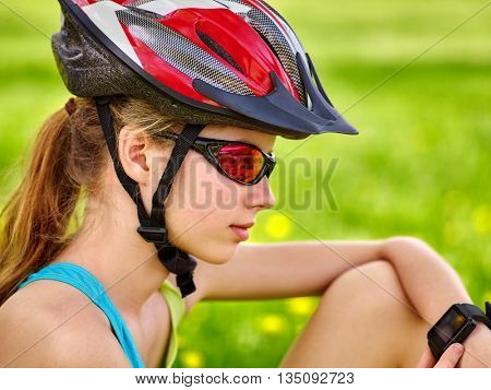 Bicyclist girl watch on smart watch. Girl counts pulse after bicycle training. Bicyclist sitting on green grass.