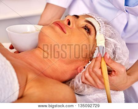 Woman middle-aged take facial mask and neck clay mask in spa salon.