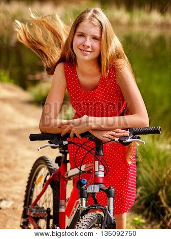 Bicycle girl. Girl wearing red polka dots dress rides bicycle into park. Girl in ecotourism. Bicycle is good for health. Bicycle girl have a long blond hair.