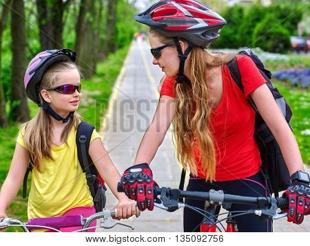 Bicycle girl. Girls wearing bicycle helmet with rucksack ciclyng bicycle. Girls children cycling on yellow bike lane. Bicycle travel.