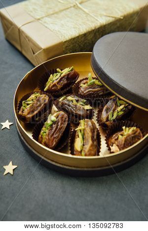 Gourmet date fruits stuffed with pistachio nuts presented in an exotic gift box. Eid festival sweet and condiments.