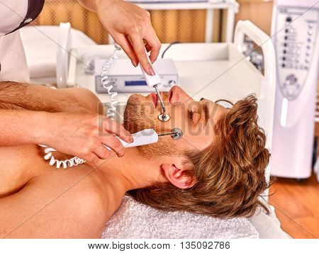 Man receiving electric galvanic facial spa massage at beauty salon. Man facial massage care.