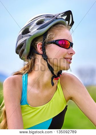 Portrait of bicycle girl. Girl wearing bicycle helmet and glasses rides bicycle aganist blue sky . Bicyclist looking up on blue sky.