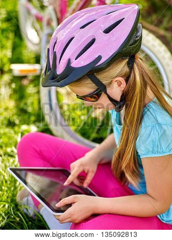 Bikes cycling girl. Girl rides bicycle. Girl wearing bicycle helmet watching at tablet pc in cycling. Bicycling touching screen by tablet pc.