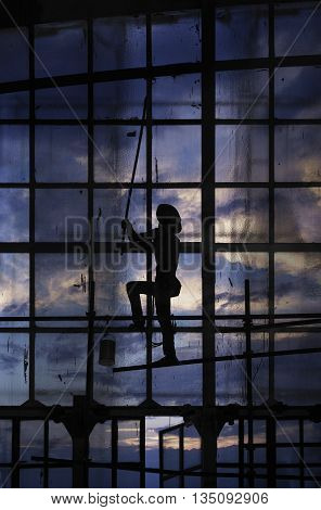 Man painting on glass window wall with paint roller over sunset sky with clouds
