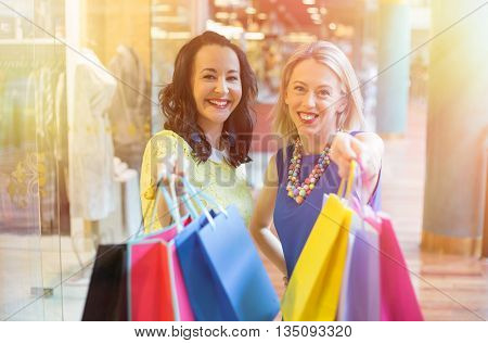 Two happy  girlfriends showing their shopping bags