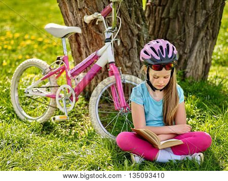 Bicycling girl. Girl rides bicycle. Girl in bicycling helmet read book on rest near bicycle. Bicyclist looking at book.