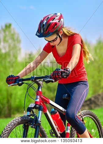 Portrait of bicycle girl. Girl rides bicycle at blue sky and green tree. Girl in bicycle. Bicycle is good for health. Bicyclist looking down.