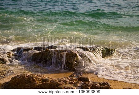 High tide wave and sand beach, tropical sea during high tide, clear salty water wave over beach stone