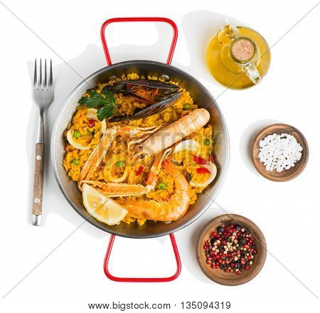 Top view of spanish paella with shrimp and mussel served with olive oil and spices isolated on white background.