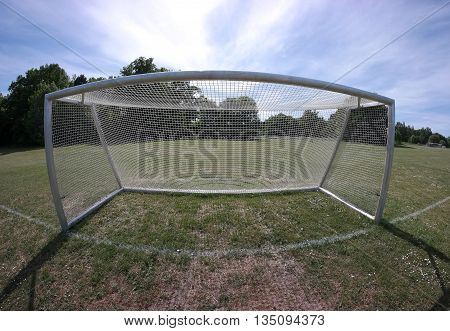 Fisheye photo of soccer goal with green grass and white lines.