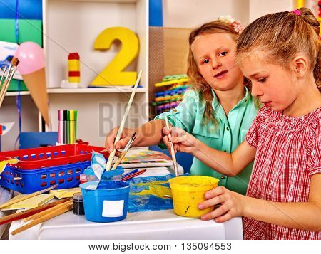 Two school girl keep brush painting on table in primary school .