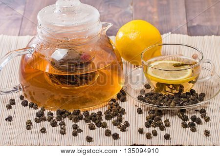 Cup of green tea with lemon on bamboo straw mat background