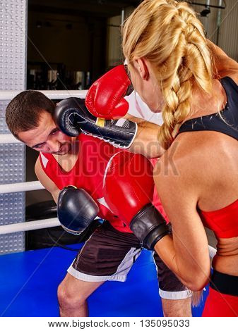Female boxer throwing right cross at head with her boxer trainer in boxer ring.