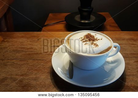 Hot Cappuccino in white cup on table.