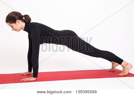Beautiful athletic girl in black suit doing yoga. Kumbhasana asana plank pose. Isolated on white background.