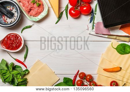 set of ingredients for cooking Italian lasagna on white wooden background top view