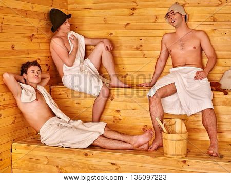 Male company in hat relaxing at sauna. Men lying on wooden boards at nature sauna.