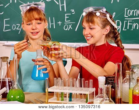 Happy children holding chemistry flask in chemistry class.