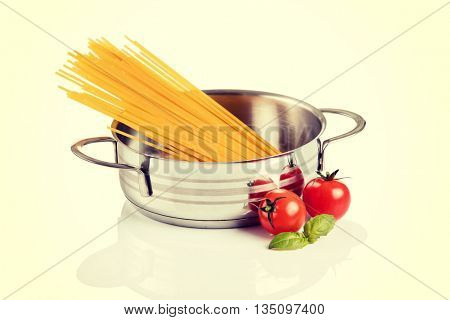 Raw pasta in metallic pot isolated on white background