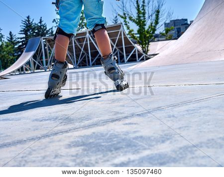 Roller skate close up in skatepark. Low section of child legs in roller skate.